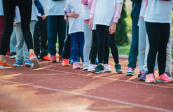 Children in ready position to run on track, closeup Royalty Free Stock Photo