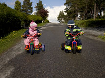 Children ready to race. Twins on tricycles ready to race down a hill Royalty Free Stock Photos