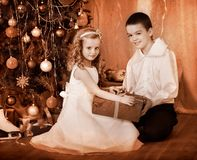 Children  receiving gifts under Christmas tree. Stock Photography