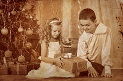 Children  receiving gifts under Christmas tree. Royalty Free Stock Photography