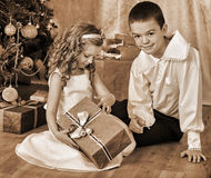Children  receiving gifts under Christmas tree Royalty Free Stock Images