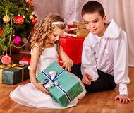 Children  receiving gifts under Christmas tree Royalty Free Stock Photos