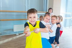 Children and recreation, group of happy multiethnic school kids playing tug-of-war with rope in gym.  stock image