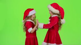 Children in red suits play New Year`s games, smile and have fun. Green screen. Children in red suits and caps play New Year games, they smile and have fun with stock video footage