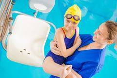 Children Rehabilitation in Pool. Children Rehabilitation Session in the Swimming Pool. Children Hospital Theme. Medical Practitioner with Young Disabled Girl on royalty free stock image