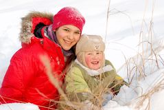 Children rejoice to the come winter. And cheerfully play white fluffy snow royalty free stock photos