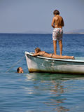 Children relaxing on boat in sea. Children (best friends) on school vacation, enjoy, swimming, sunbathing, on a small white board.Horizontal color photo Royalty Free Stock Photography