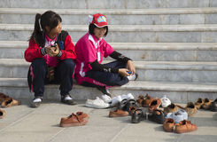 Children removing their shoes before entering building Stock Images
