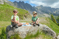 Children rest on big stone in mountains Royalty Free Stock Photos