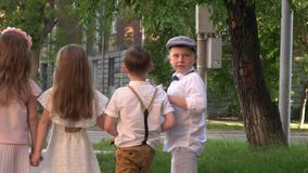 Children in a retro to clothes walk on the street. Small children the company walk in a retro to clothes down the street. Children in beautiful to clothes watch stock video