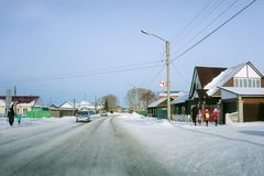 Children return from school, accompanied by their parents, on a winter day. SHARYPOVO, RF - November 23, 2017: Children return from school, accompanied by their Royalty Free Stock Photo