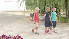 Children return to school. beginning of new school year after summer holidays. Boys and girl with school bags play among flowers n. Ear school building stock video footage
