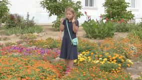 Children return to school. beginning of new school year after summer holidays. Boys and girl with school bags play among flowers n. Ear school building stock video