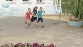 Children return to school. beginning of new school year after summer holidays. Boys and girl with school bags play among flowers n. Ear school building stock footage