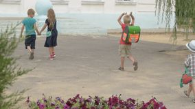 Children return to school. beginning of new school year after summer holidays. Boys and girl with school bags play among flowers near school building stock footage