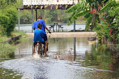 Children ride a bike through flood Stock Images