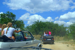 Children riding in cars on dirt road Royalty Free Stock Image