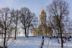 Children ride from the ice slide on a sunny winter day. Winter landscape. Temple of Holy Virgin in Dubrovitsy in the Moscow region royalty free stock images