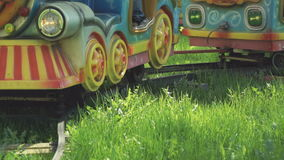 Children ride on the little electric train in park. Little children ride on attraction in the form of little electric train with the colorful railway cars stock video