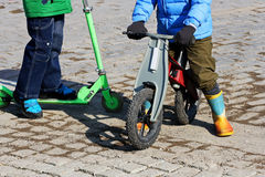 Children ride on a scooter and a balance bike. Royalty Free Stock Image