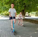 Children ride on scooters on street sidewalk in city outdoor, bright sunny day Royalty Free Stock Photo