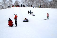 Children ride on a snow hill. Winter fun. The action takes place on the outskirts of the city of Monino. Residents of the town come with children on a snow hill stock images