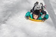 Children ride on snow saucer Stock Photo