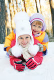 Children ride from the snow slide. Stock Photos