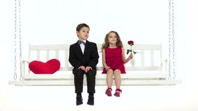 Children ride on a swing, they have a romantic relationship. White background. Slow motion