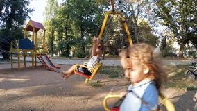 Children ride on a swing at the site. Sister and brother in playground swing outdoors stock footage