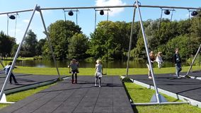 Children ride on a swing in Vondelpark stock footage