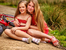 Children rides bicycle and have rest on country park road . Bicycle children. Happy sisters rides bicycle. Children have rest on country road in park. Bicycle Stock Images