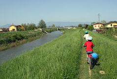 Children riding a bicycle along the banks Stock Photography