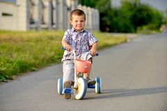 Children riding a bicycle on the street Royalty Free Stock Photography