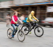 Children riding bicycles on a city street Royalty Free Stock Photos