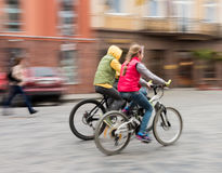 Children riding bicycles on a city street Stock Images