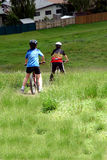 Children riding bikes on field. Rear view of two children riding bikes over field in countryside Stock Photo