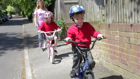 Children Riding Bikes On Their Way To School With Mother stock video