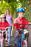 Children Riding Bikes On Their Way To School With Mother. Children Riding Bikes On Their Way To School Wearing Helmets With Mother In Background Stock Photos