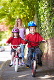 Children Riding Bikes On Their Way To School With Mother. Wearing Helmets Smiling At Camera Stock Image