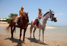 Children riding. On horseback on the beach Royalty Free Stock Image