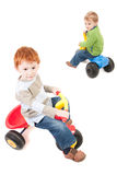 Children riding kids boys tricycles Royalty Free Stock Photo