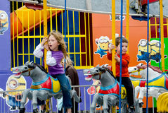Children riding merry go round horses Royalty Free Stock Photography