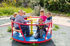 Children riding roundabout. Group of happy children riding roundabout on playground Royalty Free Stock Photography