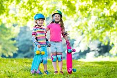 Children riding skateboard in summer park Royalty Free Stock Image
