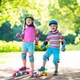 Children riding skateboard in summer park Stock Photos
