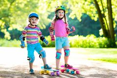 Children riding skateboard in summer park. Little girl and boy learn to ride skate board, help and support each other. Active outdoor sport for kids. Child Stock Photos