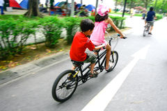 Children riding on a tandem bike. Royalty Free Stock Images
