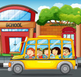 Children riding on yellow bus in town Royalty Free Stock Photos