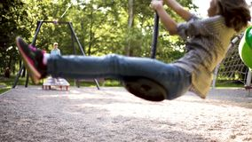 Children riding on zip line. Children having fun is riding zipline. Cute girl and teen boy moving on zip line at playground - outdoors stock video
